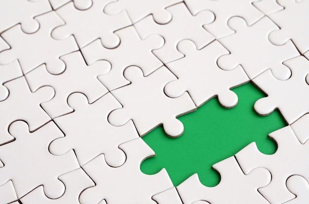 Witte puzzel in geassembleerde staat met ontbrekende elementen die een groen stootkussen voor tekst vormen