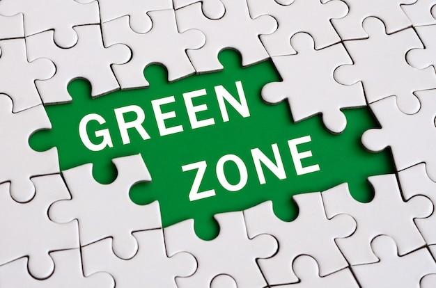 Witte puzzel in geassembleerde staat met ontbrekende elementen die een groene ruimte met witte inschrijving vormen.