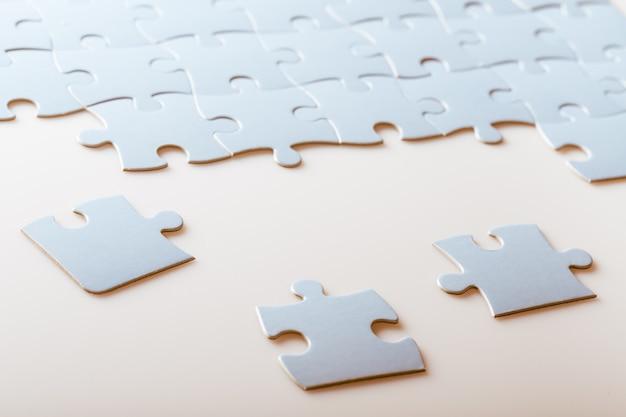 Witte puzzelstukjes op heldere tafelachtergrond