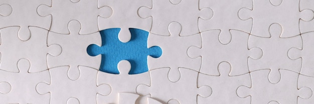 Witte puzzelstukjes zonder één stuk liggen op tafel close-up