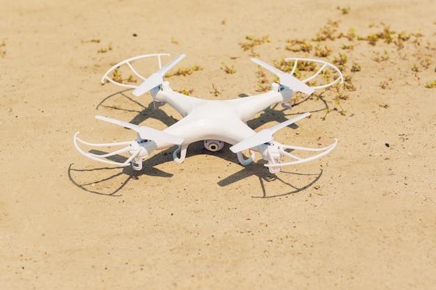 Witte quadrocopter op zand, close-up