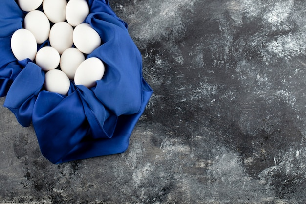 Witte rauwe kippeneieren met op een blauw tafellaken.