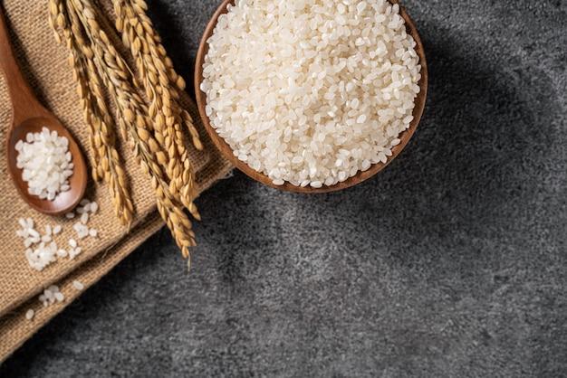Witte rauwe rijst in een kom met het oor op de donkere zwarte tafelachtergrond.