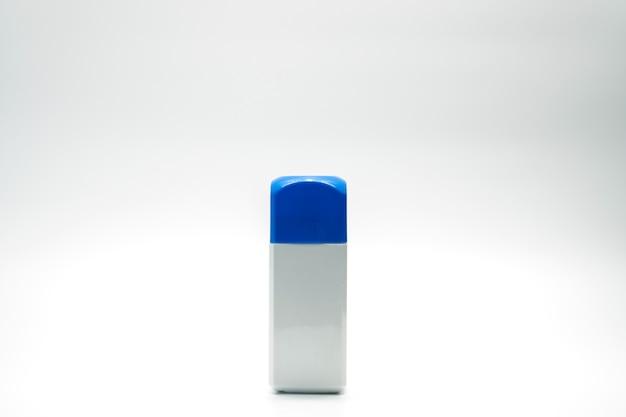 Witte rechthoekfles en blauwe dop geïsoleerd op een witte achtergrond