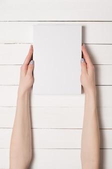 Witte rechthoekige doos in vrouwelijke handen. bovenaanzicht witte tafel de