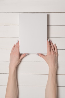 Witte rechthoekige doos in vrouwelijke handen. bovenaanzicht. witte tafel op de achtergrond