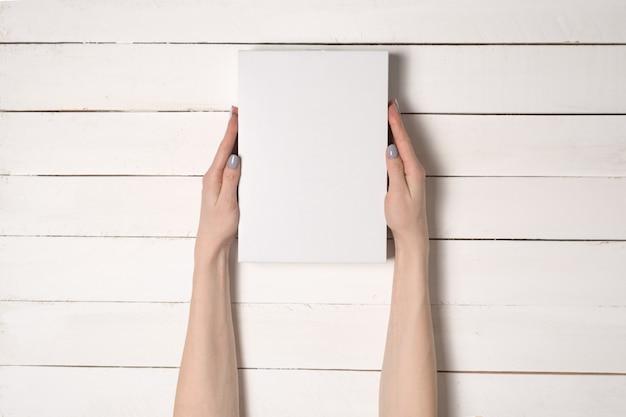 Witte rechthoekige doos in vrouwelijke handen. bovenaanzicht