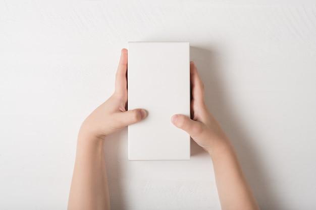 Witte rechthoekige kartonnen doos in kinderhanden.