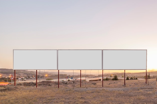 Witte reclameborden voor reclame dichtbij de weg tijdens zonsondergang