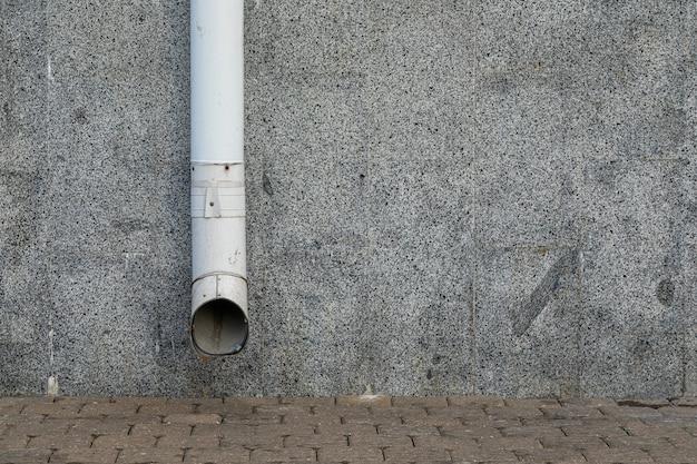 Witte regenwaterafvoer op grijze muur