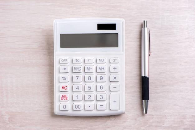 Witte rekenmachine en pen op heldere houten tafel analytics en statistieken van financiële winst investeringen risico concept kopie ruimte bovenaanzicht plat leggen