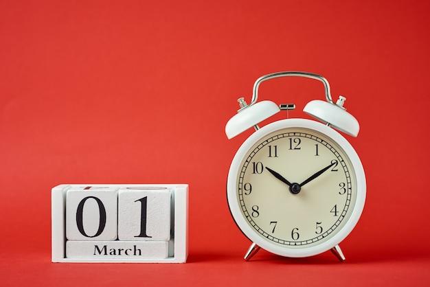 Witte retro wekker met bellen en houten kalenderblokken met datum 1 maart op rood