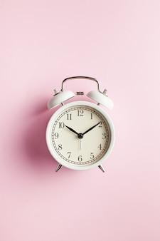 Witte retro wekker op een roze ondergrond met kopie ruimte