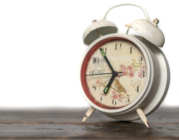 Witte retro wekker verafgood op kleurrijke achtergrond op houten oppervlak b