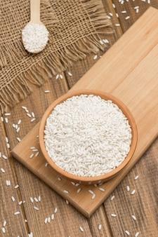 Witte rijst in ceramische kom. rijst in houten lepel. rijst wordt op tafel verspreid. houten tafel. plat leggen