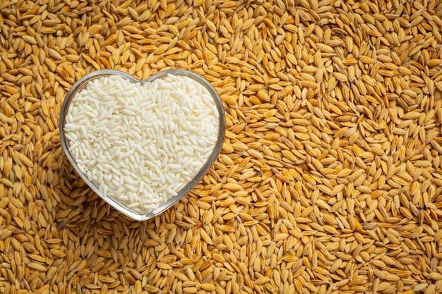 Witte rijst in hartvormige kom op de vloer vol padie