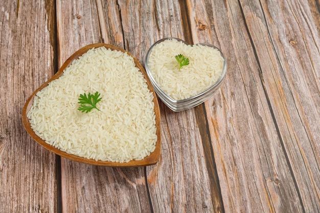 Witte rijst wordt in een kopje op de houten vloer gelegd.