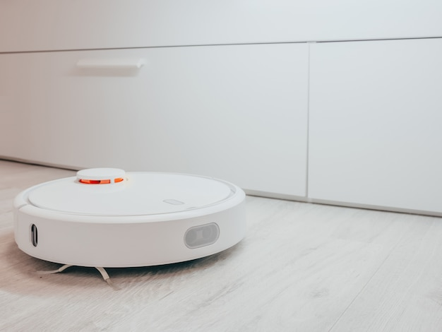 Witte robot stofzuiger op een laminaat op een wit bed