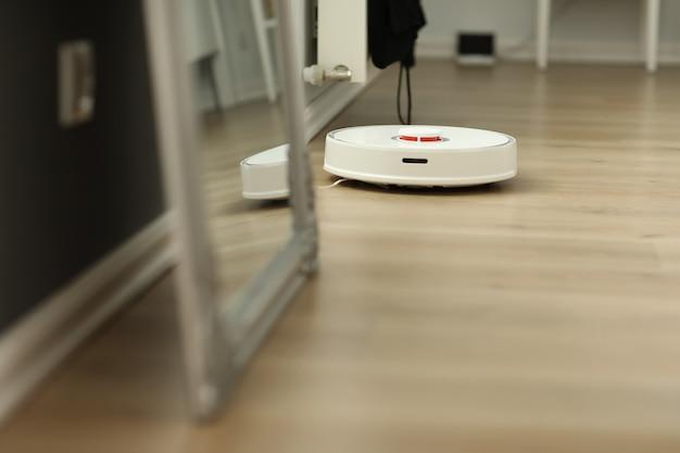 Witte robotstofzuiger. de robot wordt bestuurd door spraakopdrachten voor directe reiniging.