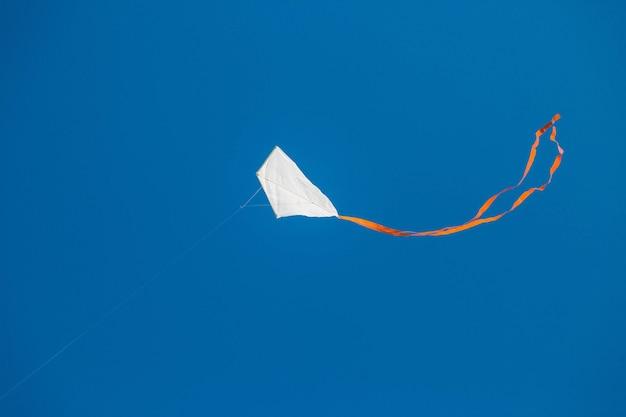 Witte rode de steel verwijderde van vlieger die tegen blauwe duidelijke hemel vliegt.