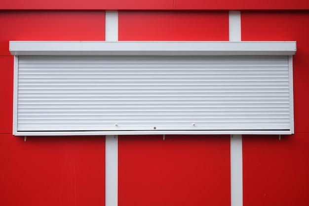 Witte rolluiken bij een rode kiosk.