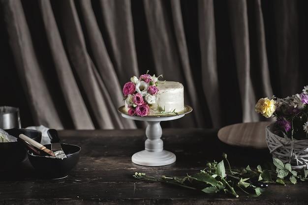 Witte romige cake versierd met rozen in donker interieur
