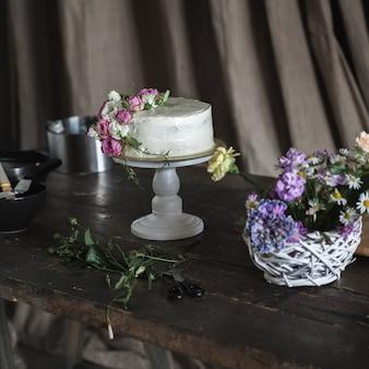 Witte romige cake versierd met rozen op donkere achtergrond