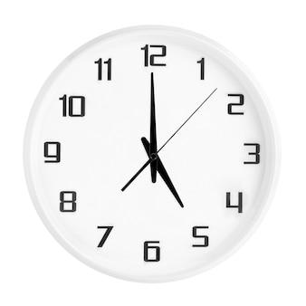 Witte ronde bureauklok die vijf uur toont die op wit wordt geïsoleerd. lege witte klok met 17:00 of 05:00 uur