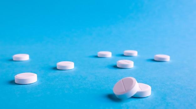 Witte ronde medische pillen op een blauwe achtergrond. verspreide witte pillen op tafel. het concept van geneeskunde, apotheek en gezondheidszorg. ruimte kopiëren lege ruimte voor tekst of logo.