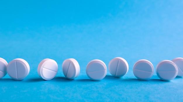 Witte ronde medische pillen op een blauwe ruimte. verspreide witte pillen op tafel