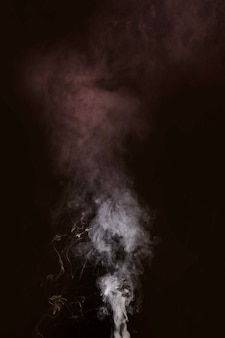 Witte rook die tegen zwarte achtergrond blaast