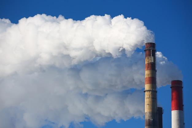 Witte rook komt uit leidingen tegen de blauwe hemel