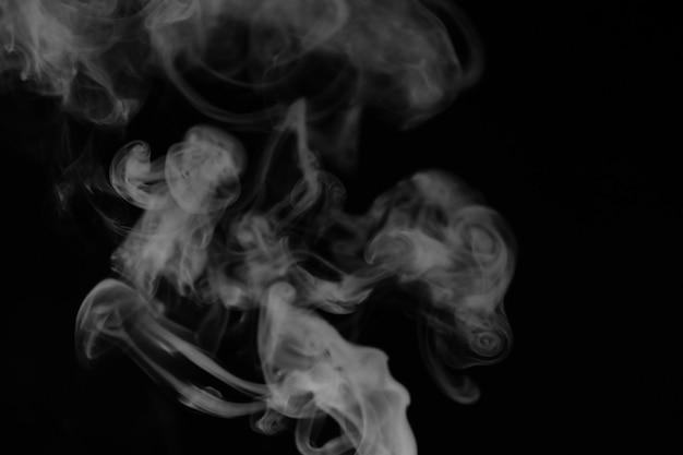 Witte rook op een zwarte achtergrond. textuur van rook. clubs van witte rook op een donkere achtergrond voor overlay
