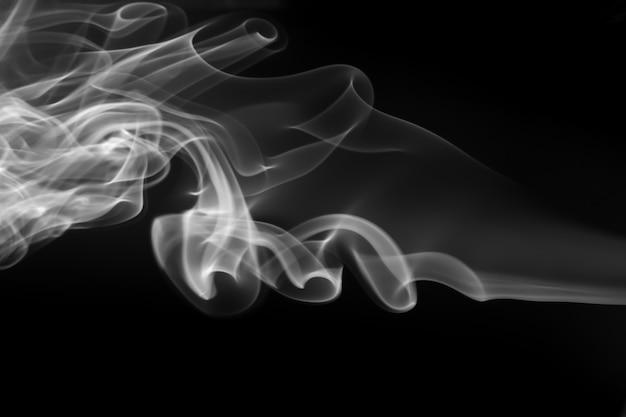 Witte rooksamenvatting op zwarte achtergrond, duisternisconcept