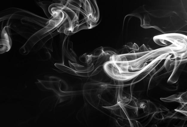 Witte rooksamenvatting op zwarte achtergrond. vuur. duisternis concept
