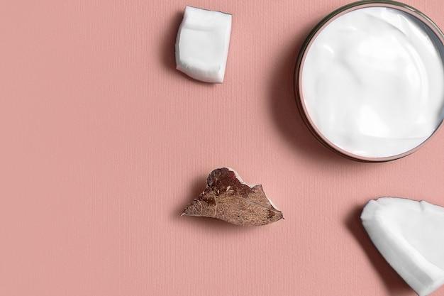 Witte room in een pot met kokos op trendy roze. schoonheid en gezondheidszorgconcept. minimalistische plat lag met kopie ruimte. bovenaanzicht. cosmetische natuurlijke huidverzorging
