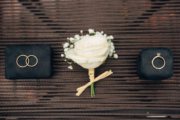 Witte roos corsages tussen trouwringen en een verlovingsring met een grote edelsteen