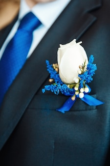 Witte roos en blauwe delphinium corsages bloem op bruidegom bruiloft jas met blauwe stropdas