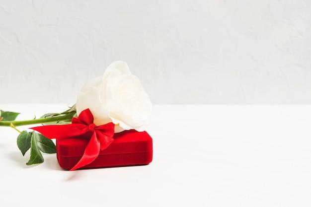 Witte roos en rode geschenkdoos voor sieraden