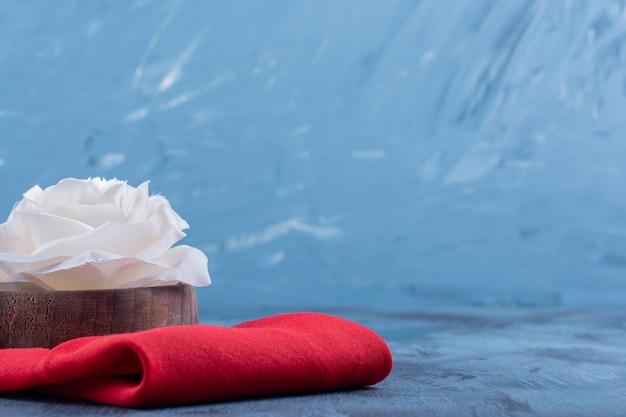 Witte roze bloem op rood tafelkleed op blauw.