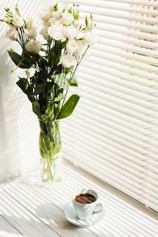 Witte roze bloemenvaas en koffiekop dichtbij vensterzonneblinden