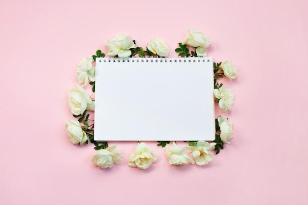 Witte rozen en notitieblok