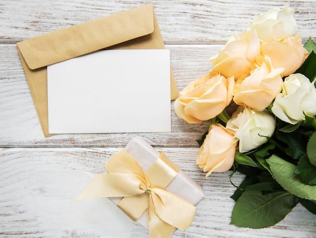 Witte rozen en wenskaart op een oude houten tafel