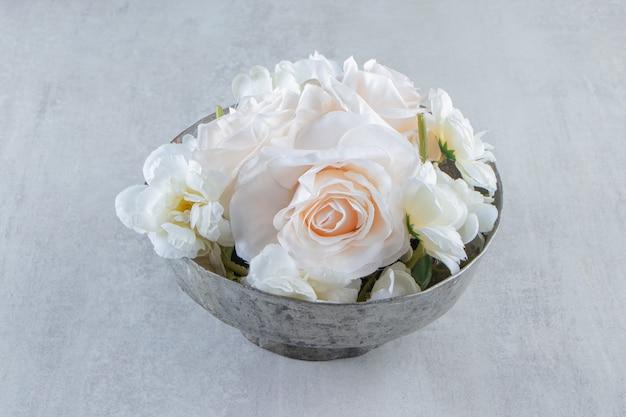 Witte rozen in een ijzeren kom, op de witte tafel.