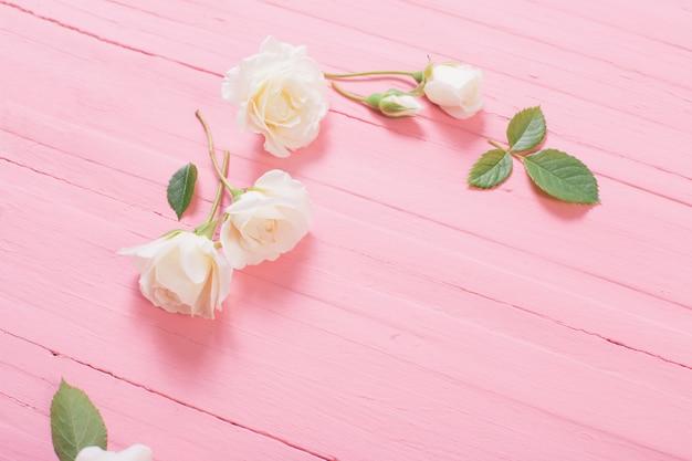 Witte rozen op roze houten achtergrond