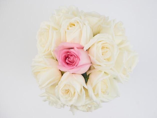 Witte rozenbloemen en één roze roze bloem