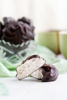 Witte russische marshmallow in chocolade in kom op een houten tafel. het stilleven, selectieve aandacht. verticaal