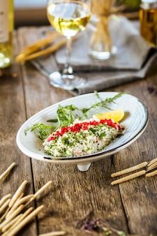 Witte salade met rode kaviaar tobiko en groene ui