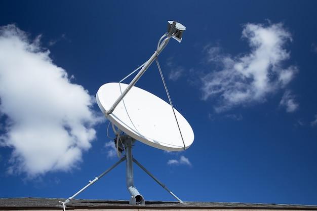 Witte satellietschotel met blauwe hemel