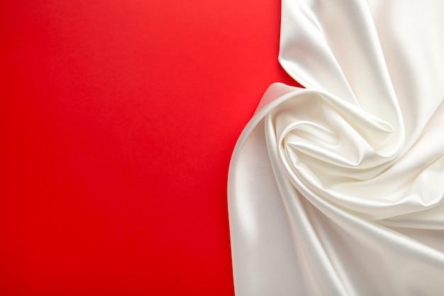Witte satijnen stof op rode achtergrond